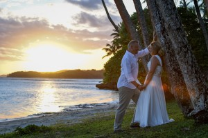 The newly weds cosy up against a palm tree during a fiery Fiji sunset