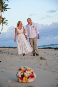 The newly weds hold hands as they stroll on the beach