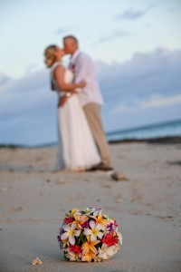 A blurred kiss with tropical Fiji flower bouquet in the foreground