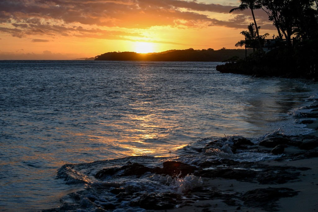 A breathtaking and golden Fiji sunset over hills of the Pacific Fiji