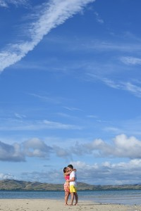 The couple passionately kiss against the deep blue skies of Nadi Fiji