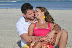 The couple laughs while seated on the beige beaches of Nadi Fiji