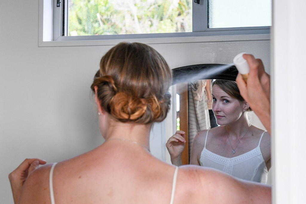 The bride sprays her hair in the mirror