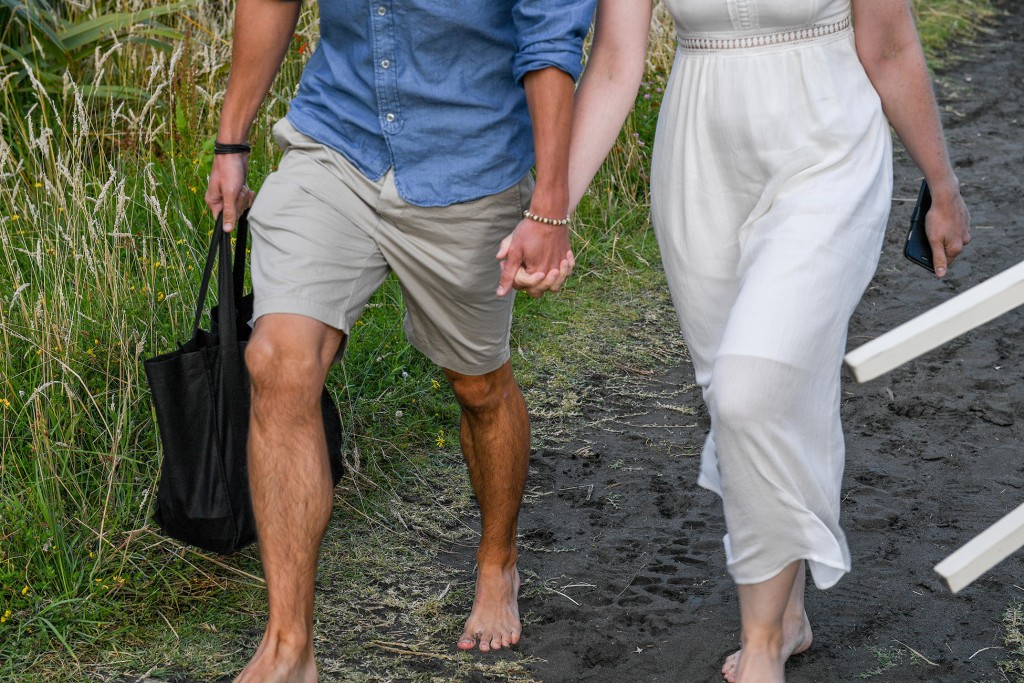 The married couple walks hand in hand on the black sand beach at Karekare
