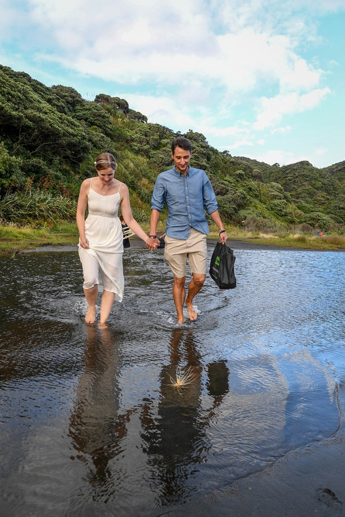 The married couple wade through the shallow waters at Karekare black sand beach