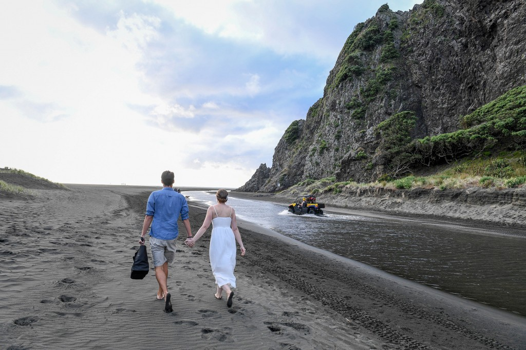 The married couple hold hands as they walk on the black sand beach of Karekare beach