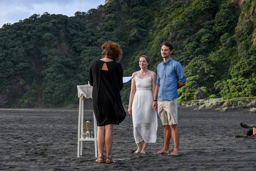 The celebrant leads the marriage ceremony on the black sand beach