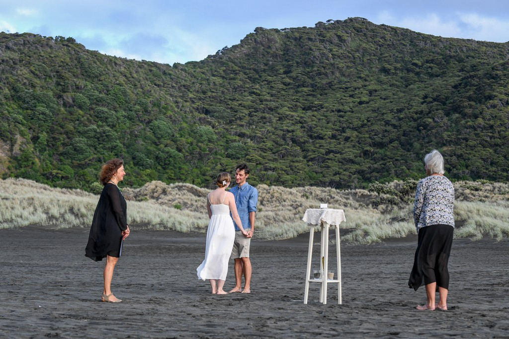 The couple exchanges vows on black sand Karekare beach