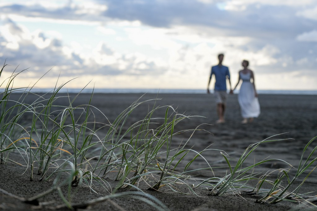 An out of focus image of the newly weds on the black sand beach