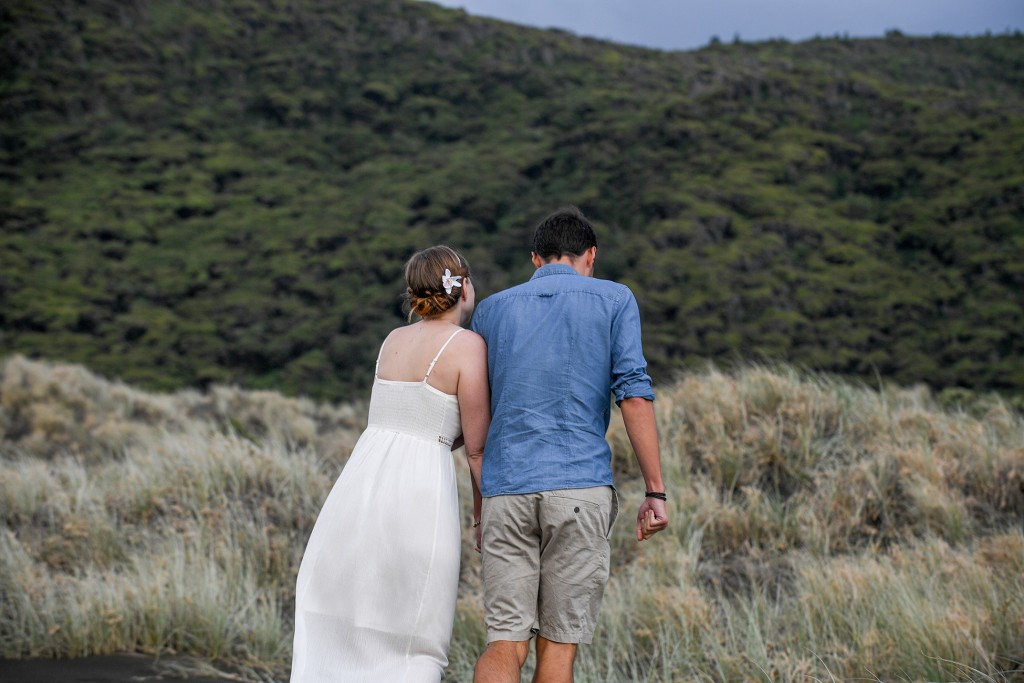 The couple walks towards the rolling green hills of Karekare beach