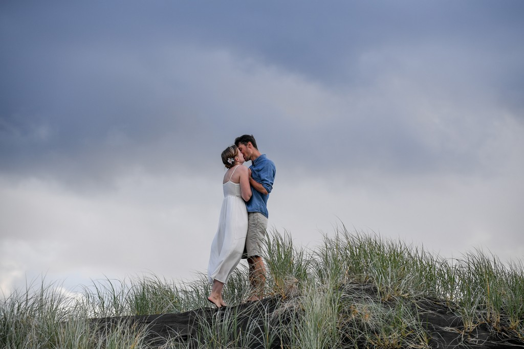 The married couple kiss on a hill against a deep grey sky