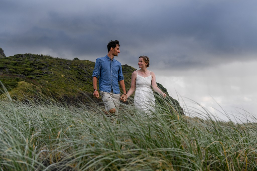 The newly weds walk through patches of grass