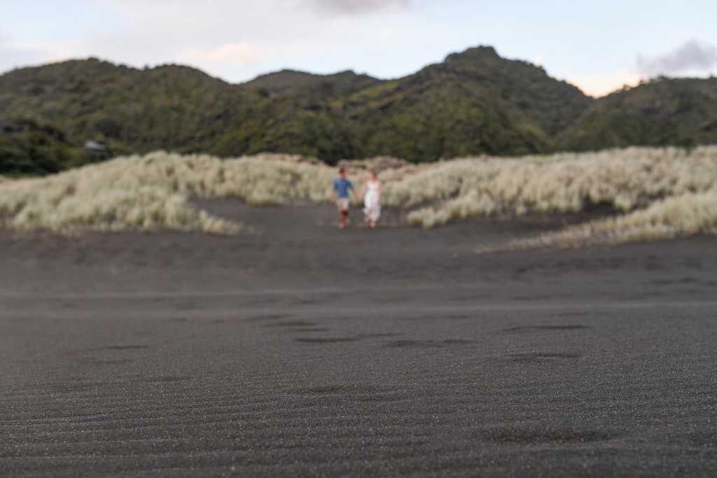 An out of focus image of the couple standing in black sand