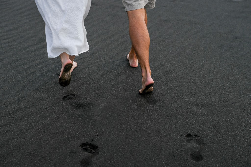 The newly weds leave footprints in the black sand at Karekare