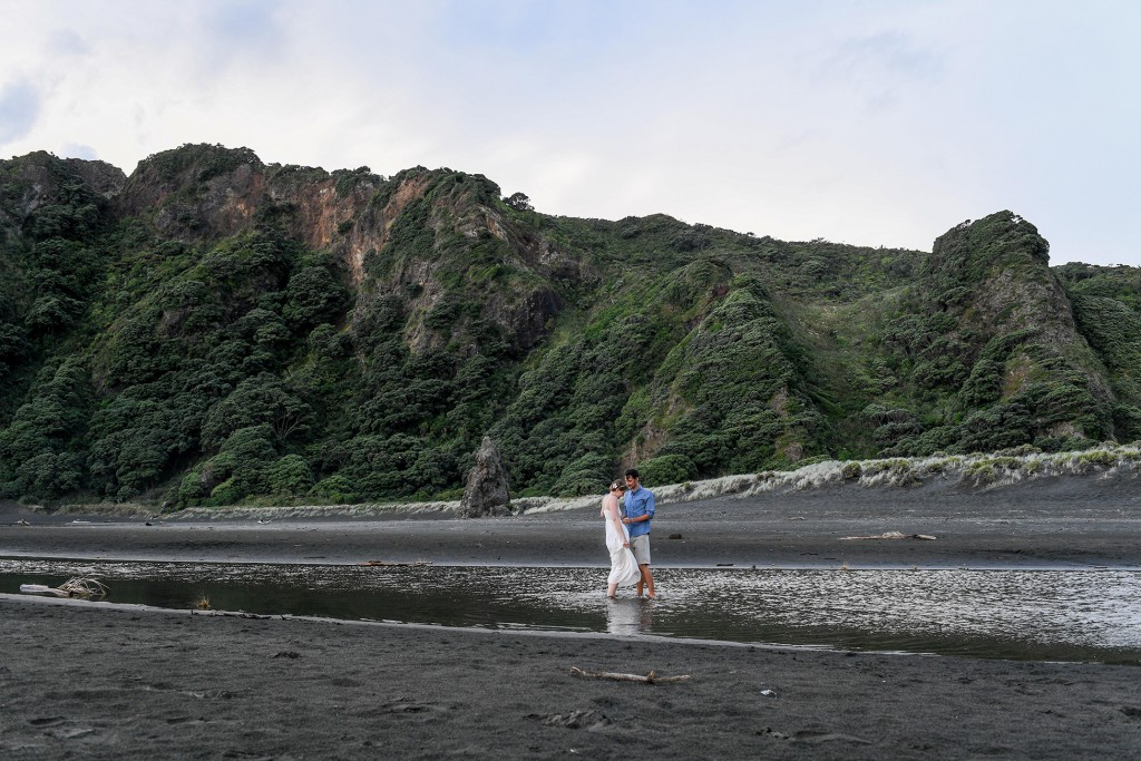 The newly weds stroll in the river at Karekare beach