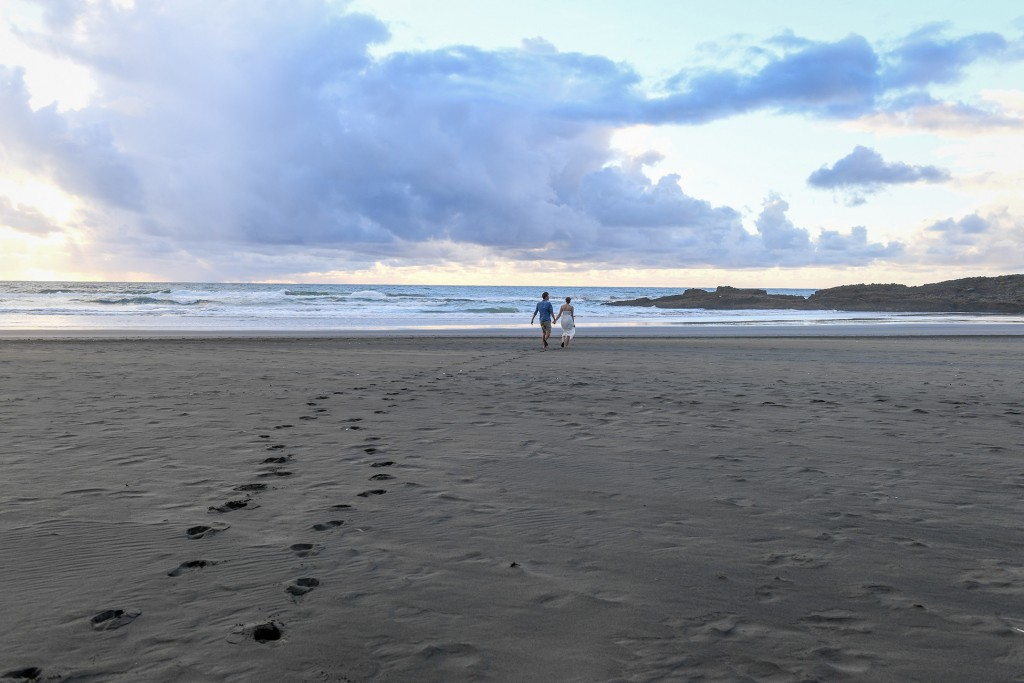 The newly weds stroll on black sand beaches
