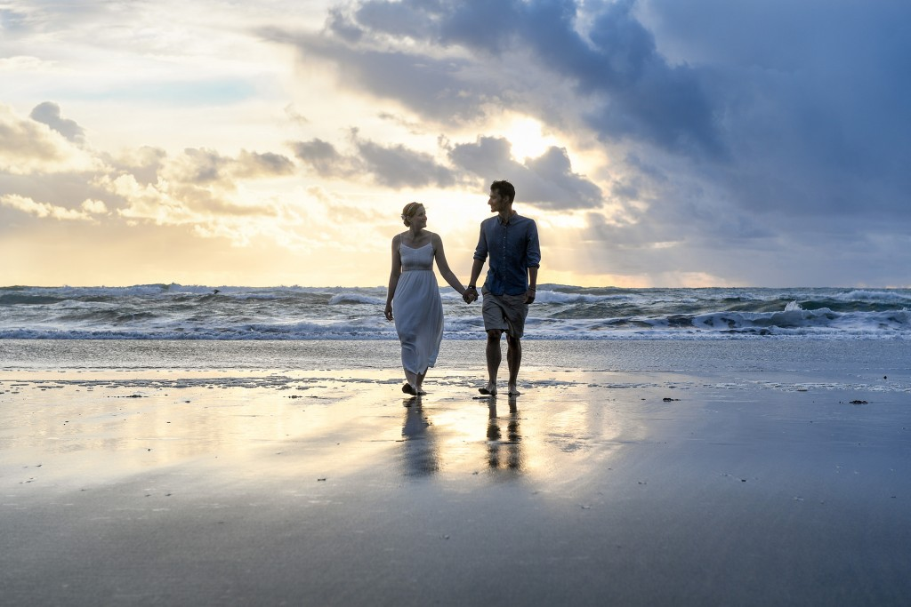 Newly weds walk against a golden sunset in the horizon