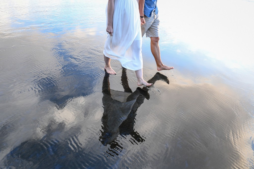 A reflection of the newly weds walking on sand in Karekare