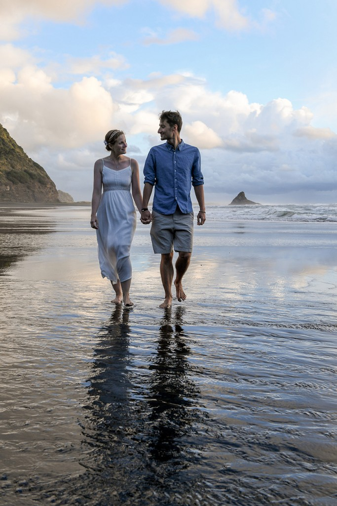 The newly weds hold hands as they walk in shallow Karekare beach