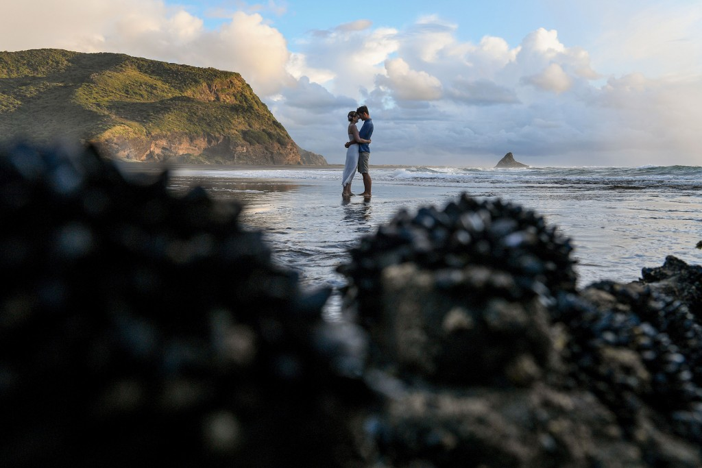 A long shot of the newly weds standing in the black sand beach