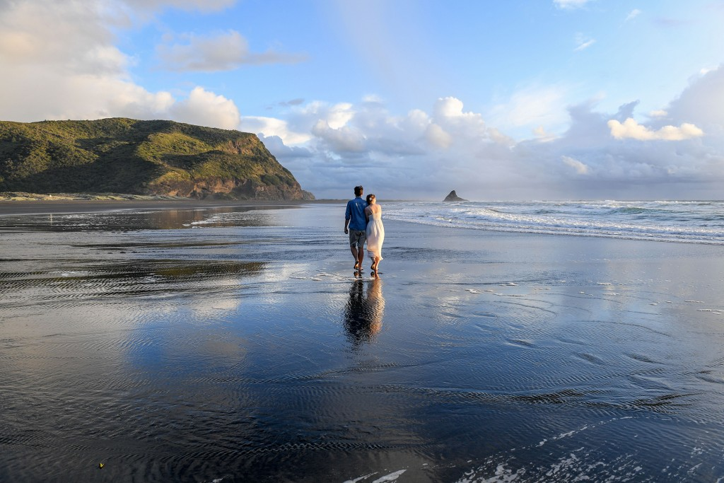 The couple holds hands standing in breathtaking nature at Karekare beach