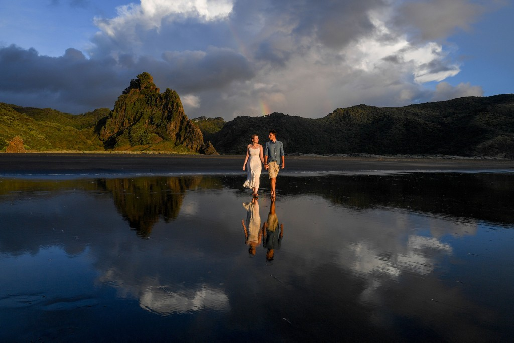 The newly weds stroll on black sand beaches at Karekare