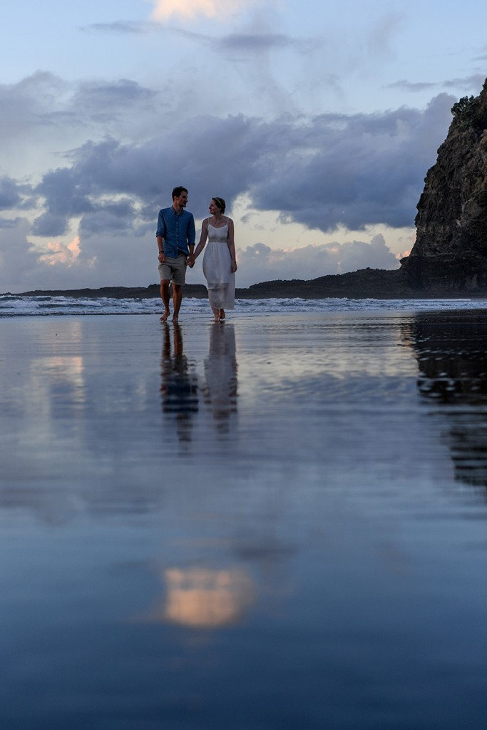 The newly weds stroll on the shallow waters of the black sand beach at Karekare
