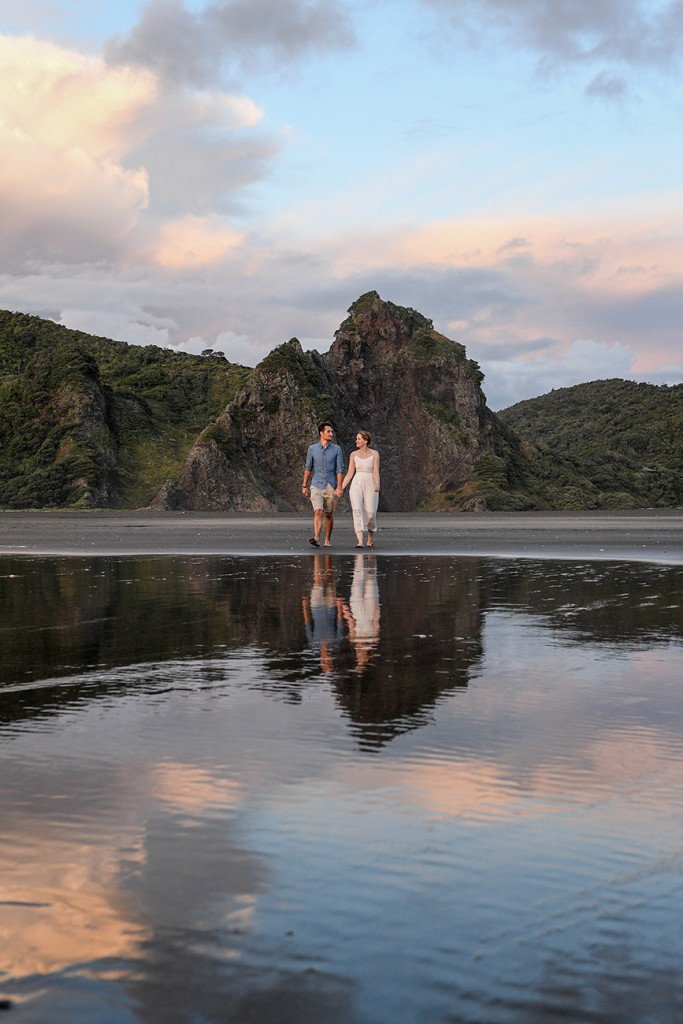 The married couple stroll at the edge of black sand beach