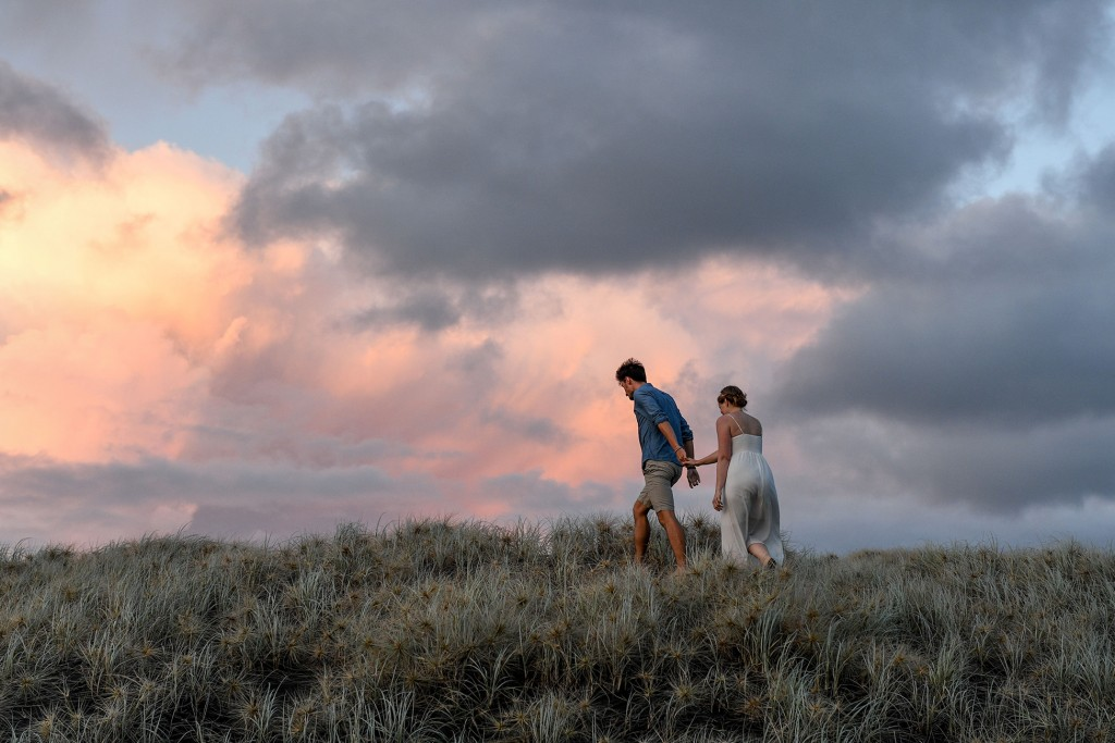 The newly weds walk over a hill at Karekare during sunset