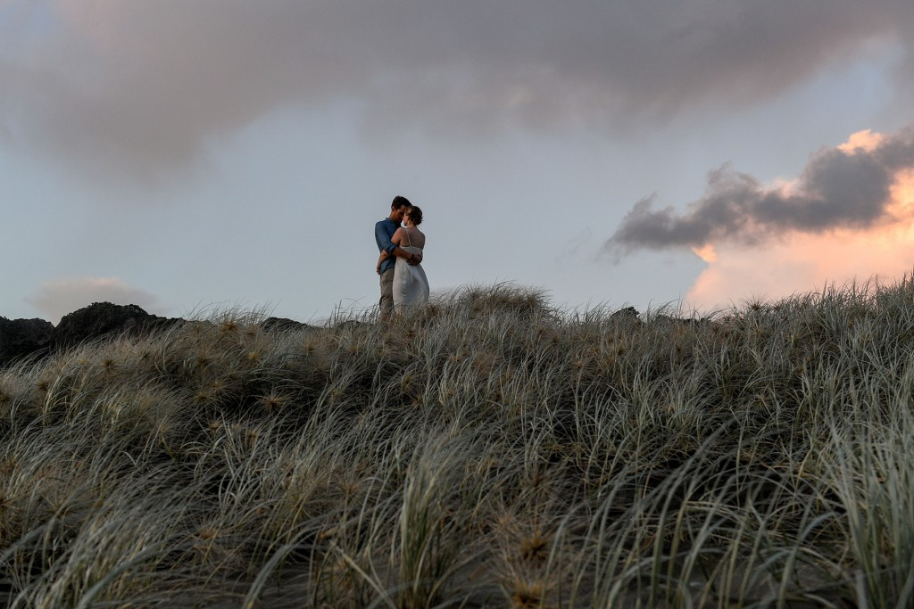The newly weds hug on a lonely hill at sunset