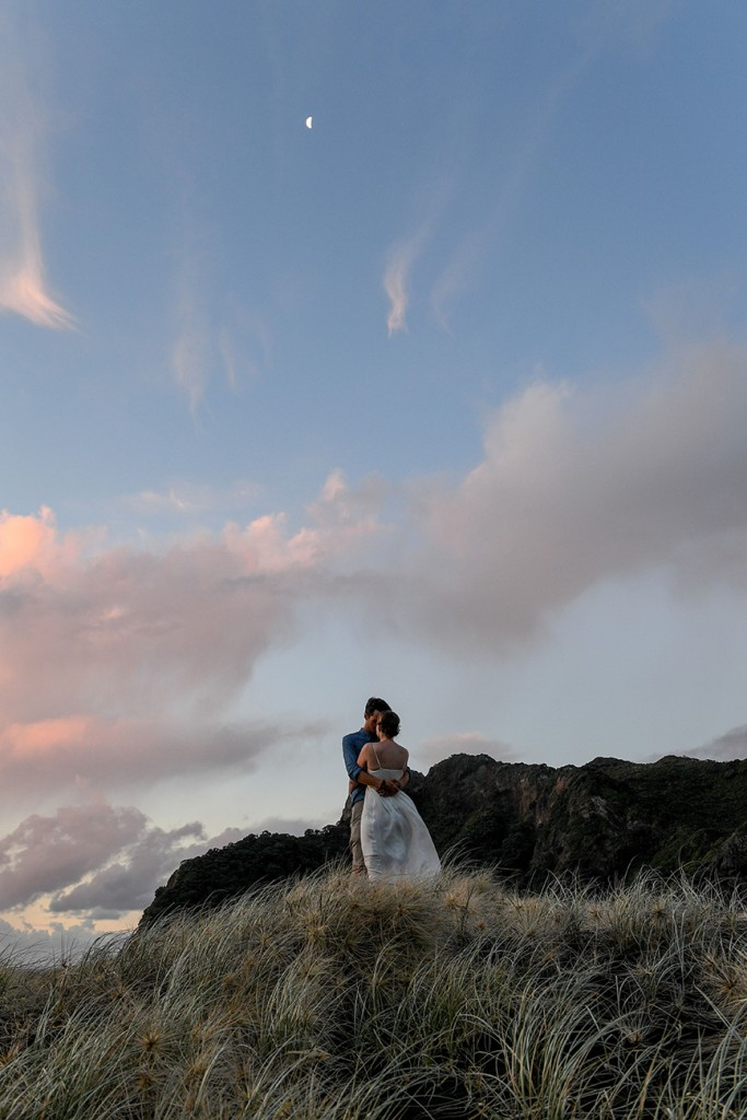 The couple stand against the enormous backdrop of a pink sunset