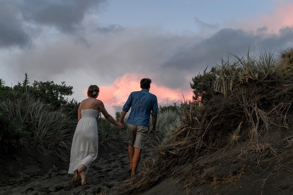 The couple hold hands as they walk over the hills