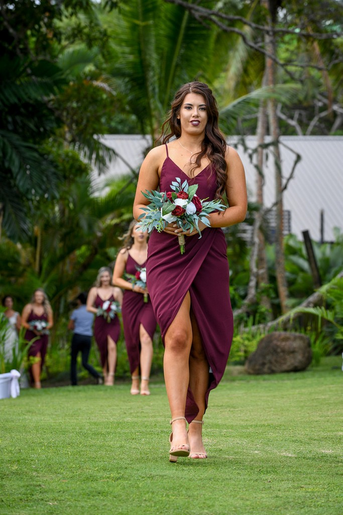 A stunning bridesmaid in a burgundy dress walks down the aisle