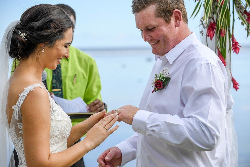 The bride slips the ring onto her groom's finger