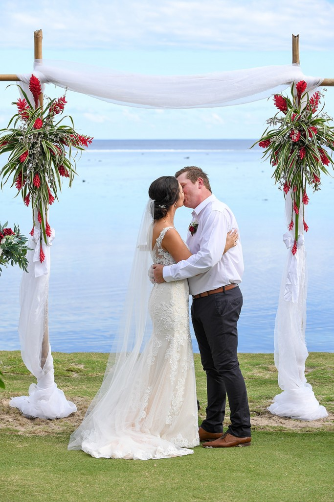 The newly weds kiss at the altar overlooking the Pacific ocean