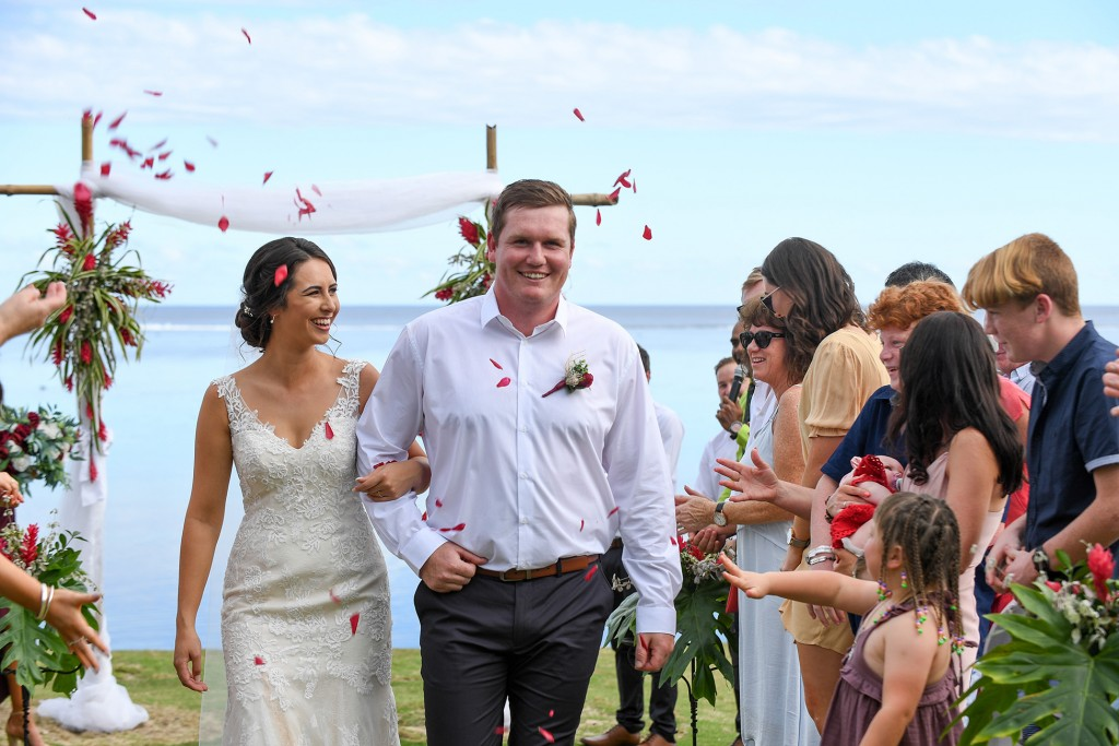 Red rose petals are thrown over the newly weds as they walk down the aisle