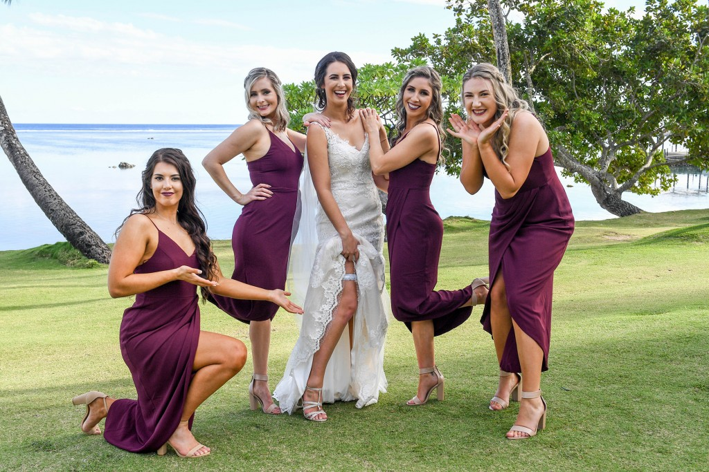 The bride happily poses with her bridesmaids