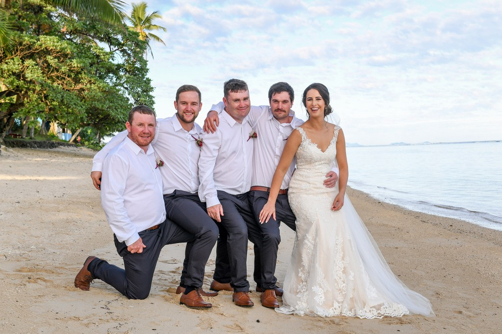The bride poses with the groomsmen at the beach