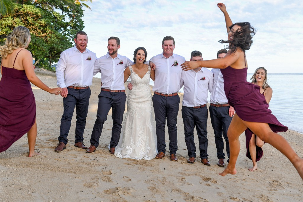A bridesmaid photobombs the bride's and groomsmen's photo