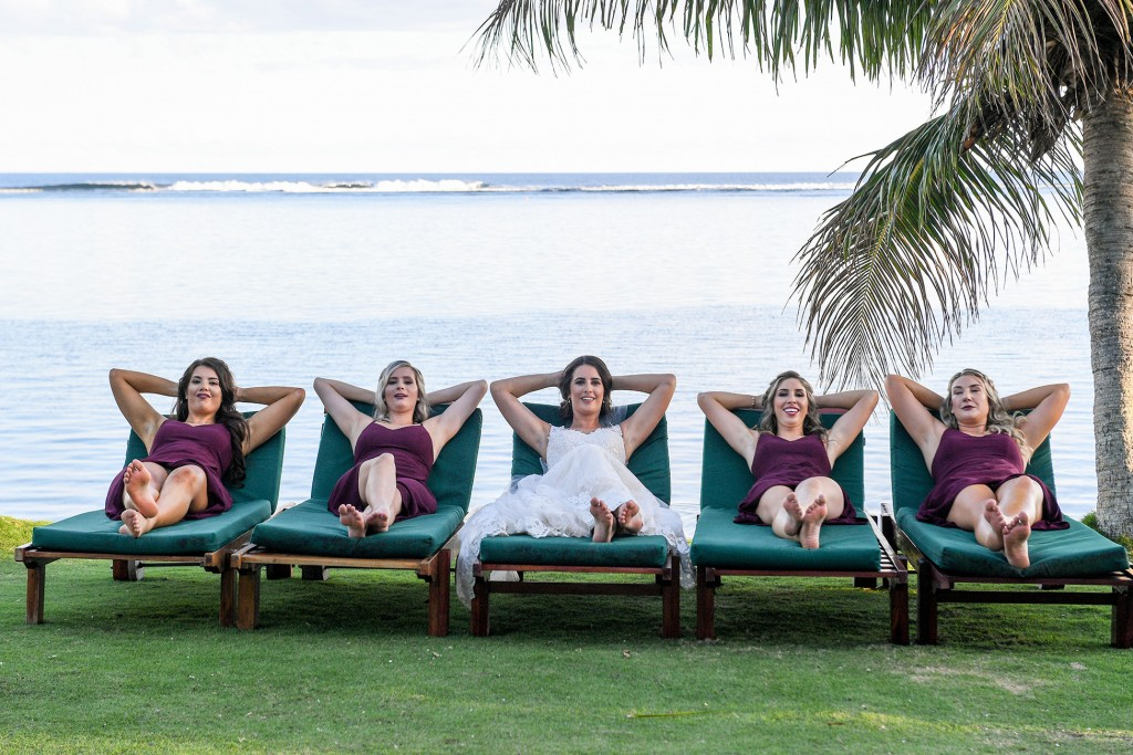 The bridesmaids relax on lounge chairs at the beach