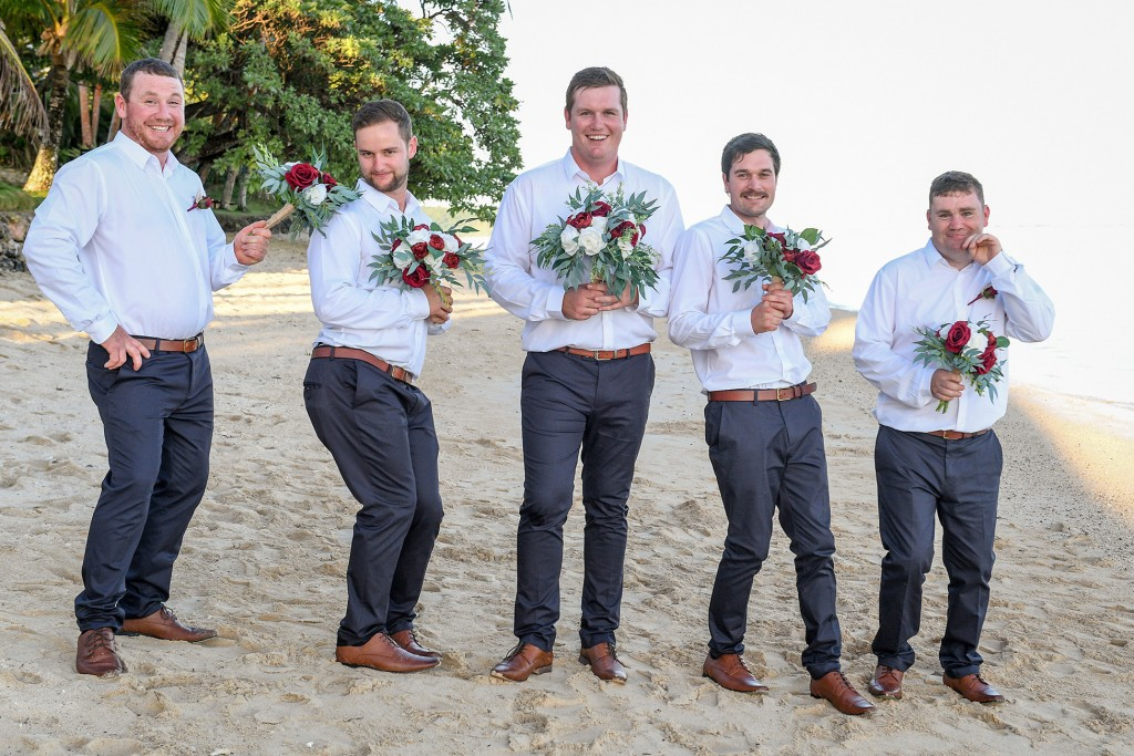 The groomsmen pose with flowers on the beach