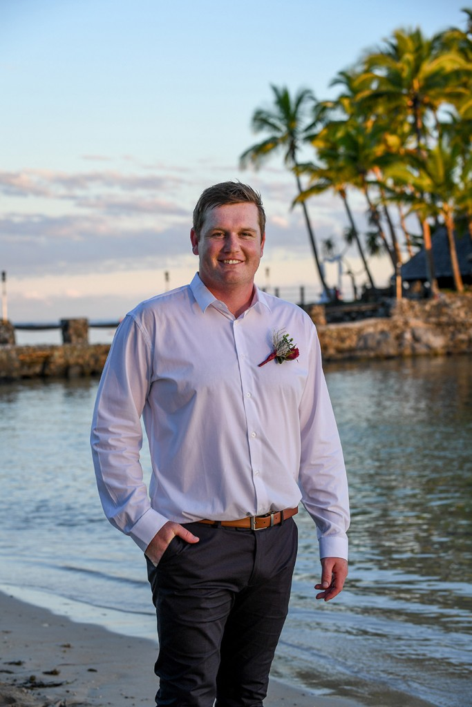 A portrait of the dapper groom posing at the edge of the beach at Warwick Fiji