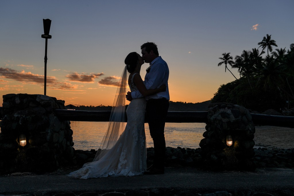 A silhouette portrait of the newly weds kissing at sunset in Warwick Fiji