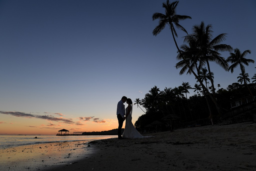 A silhouette photo of the newly weds and the palm trees at sunset