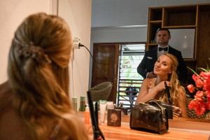 A reflection of the groom checking out her bride as she curls her hair in the mirror