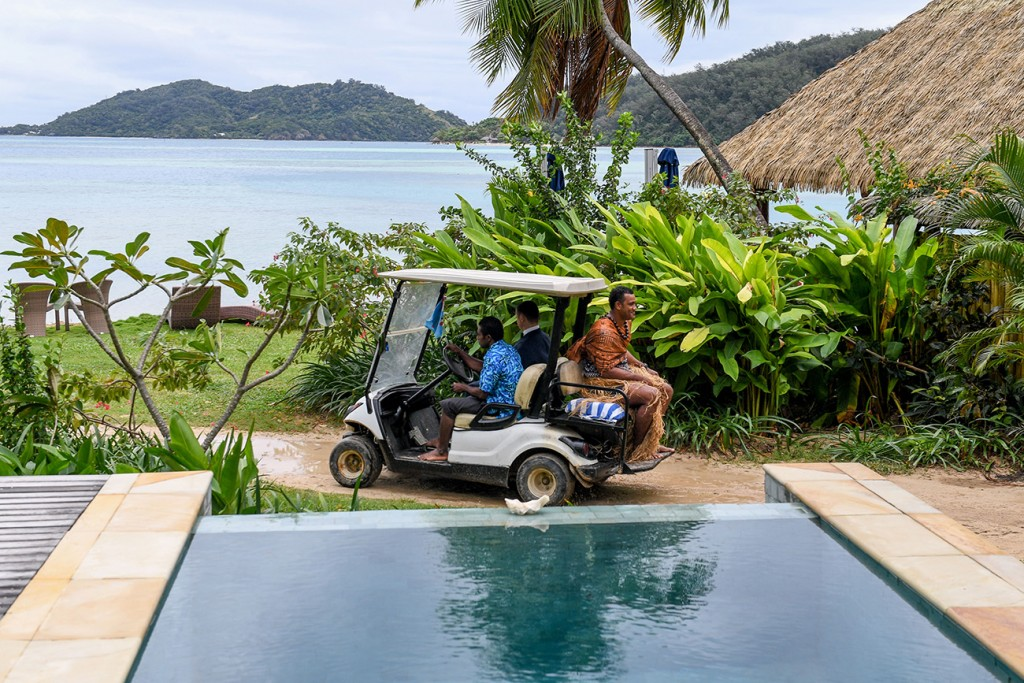 The groom and a Fiji warrior get a ride on a golf cart to the wedding ceremony