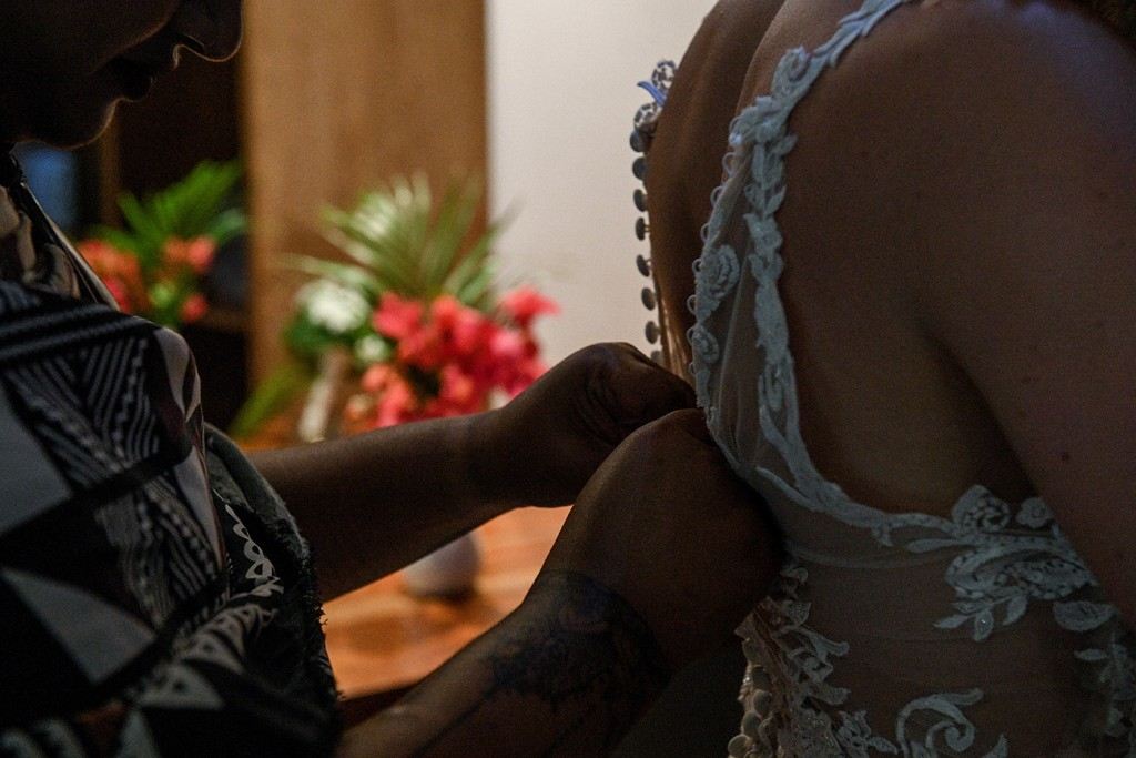 A closeup of the bride being helped into her wedding gown