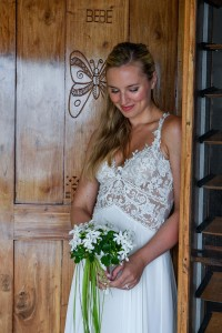 The bride poses in front of the butterfly door at Tropica Island Resort
