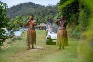 The bride arrives in a golf cart led by traditional Fiji warriors