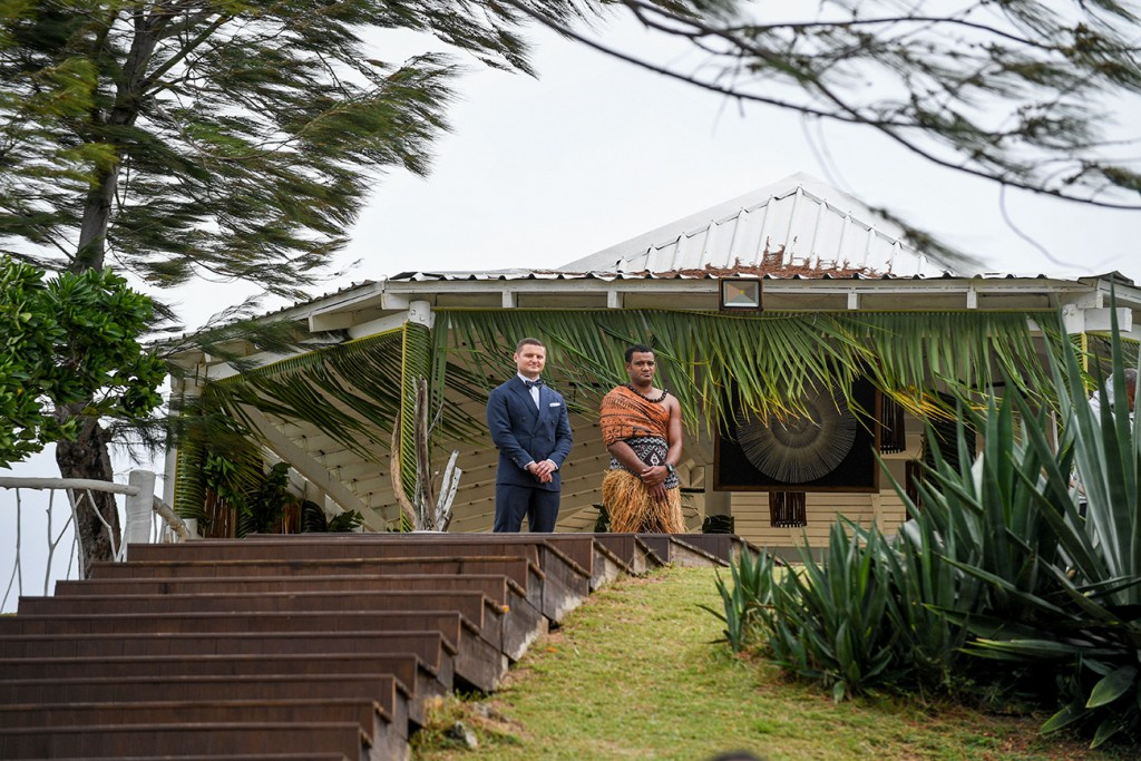 The groom and a traditional Fiji warrior await the bride